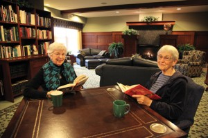 Two women at table in handsome library
