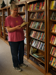 Woman standing at library shelves